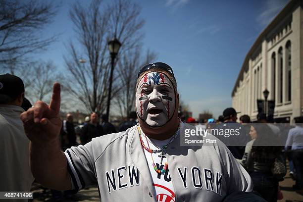 Yankee fan with a painted face pauses at Yankee Stadium for the Home Opener between the New York Yankees and the Toronto Blue Jays on April 6 2015 in...