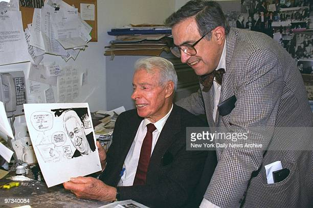 Yankee legend Joe DiMaggio looks at a cartoon of himself drawn by cartoonist Bill Gallo during his visit to the Daily News Joe is in town for the...