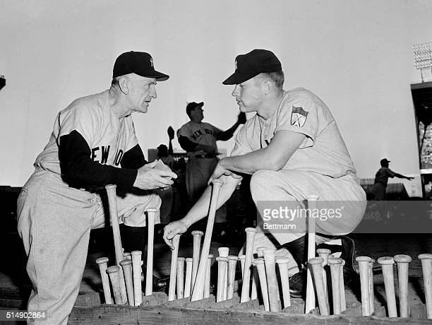 Yankee manager Casey Stengel seems to be giving Mickey Mantle some advice as they confer over the bat rack at Cleveland Municipal Stadium before the...