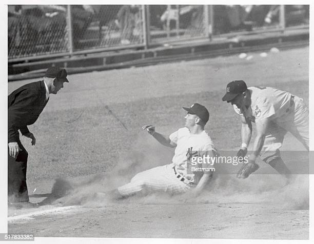 Yankee outfielder Irv Noren advancing from first to third on Carey's single beats the peg to Al Rosen of the Indians who tries for the tag Ump...