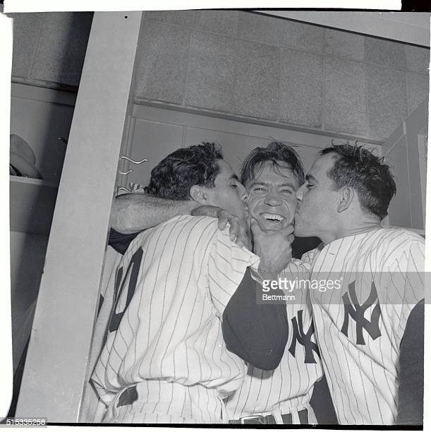 Yankee shortstop Phil Rizzuto and catcher Yogi Berra plant kisses on the beaming face of outfielder Hank Bauer who made the sensational 3rd out catch...