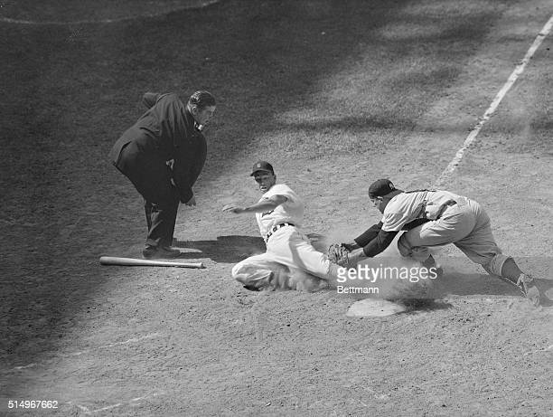 Yankees' catcher Yogi Berra stretches as he tags Detroit's Bill Tuttle from third base on Reno Bertoia's slow roller down the third-base line in the...