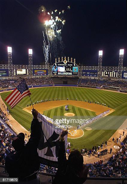 Yankees' fans Aric Hoad and Amy Stillwell cheer as fireworks light up the sky over Comiskey Park in Chicago for the start of the game 18 September...