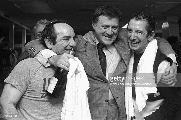 Yankees' owner George Steinbrenner hugs coach Yogi Berra and manager Billy Martin as they celebrate victory with champagne