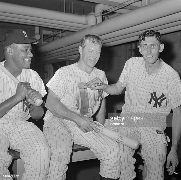 Yankee's pitcher Jim Coates gives Mickey Mantle a dusting as Elston Howard smiles his approval in dressing room of Yankee Stadium here after...