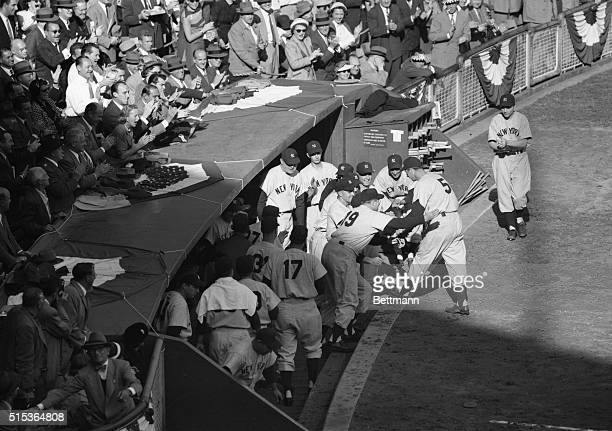 Yankees swarm from the dugout to congratulate Joe DiMaggio after he poled a tworun homer into the upper leftfield stands in the fifth inning of the...