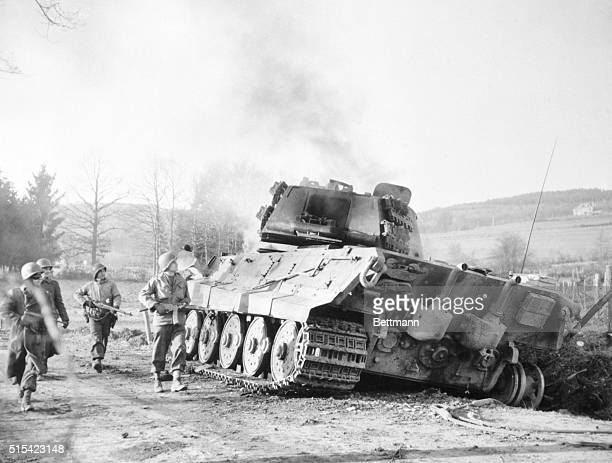 Yanks look up with satisfaction as they pass a burning German Tiger tank on their way to La Gleize Belgium which was recaptured during the current...
