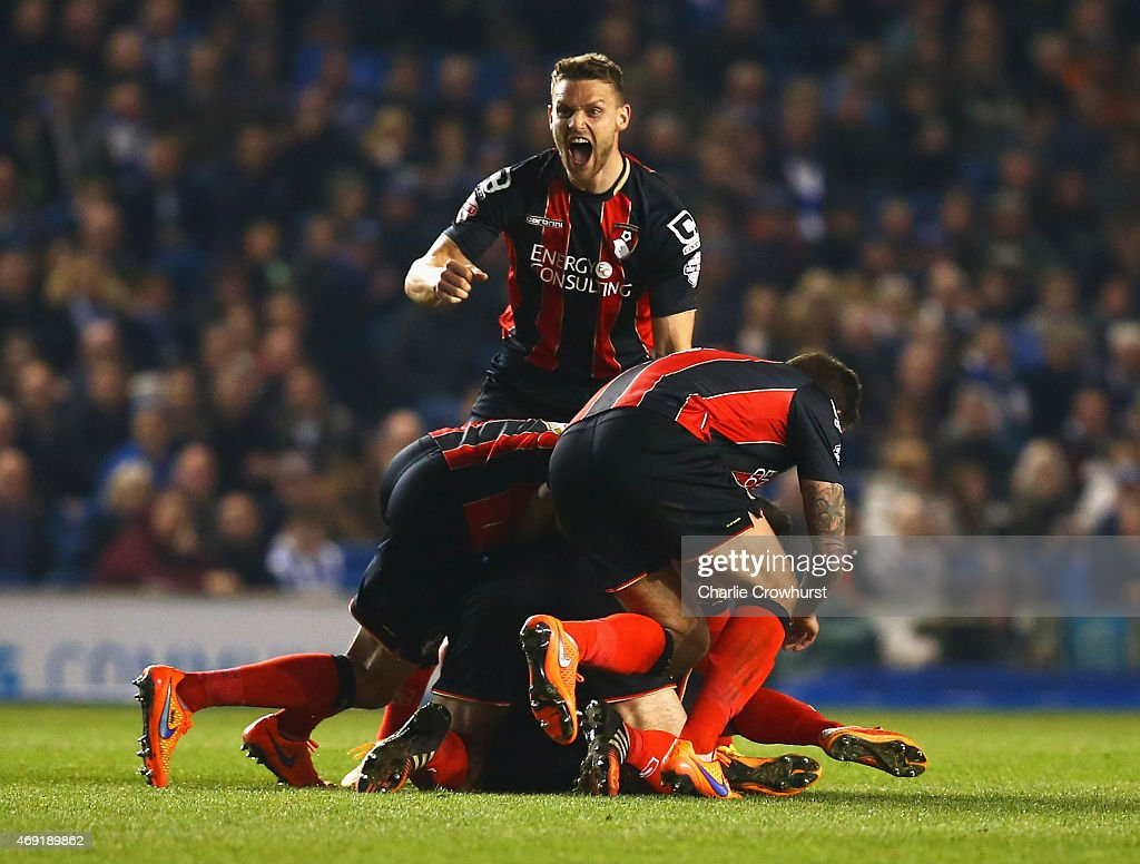 Yann Kermorgant of Bournemouth (obscured) is mobbed by team mates in celebration as he scores their first goal from a free kick during the Sky Bet Championship match between Brighton & Hove Albion and AFC Bournemouth at Amex Stadium on April 10, 2015 in Brighton, England.