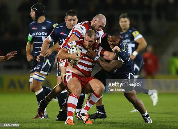 Yann Thomas of Gloucester Rugby is tackled by Halani Aulika of Sale Sharks during the Aviva Premiership match between Sale Sharks and Gloucester...