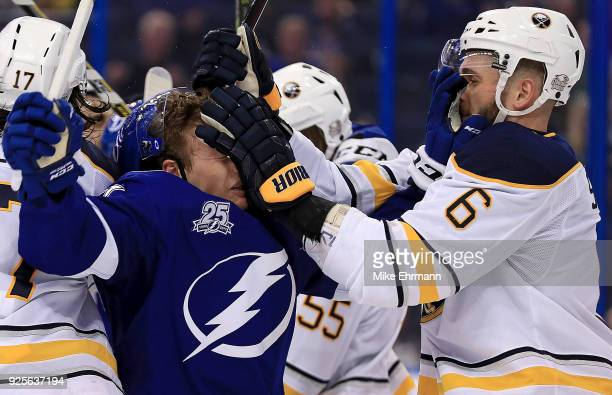 Yanni Gourde of the Tampa Bay Lightning and Marco Scandella of the Buffalo Sabres get in a fight during a game at Amalie Arena on February 28 2018 in...