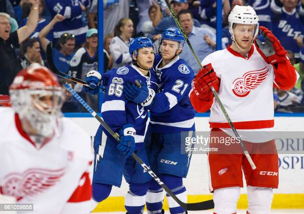 Yanni Gourde of the Tampa Bay Lightning celebrates his goal with teammate Brayden Point against goalie Petr Mrazek and Nick Jensen of the Detroit Red...