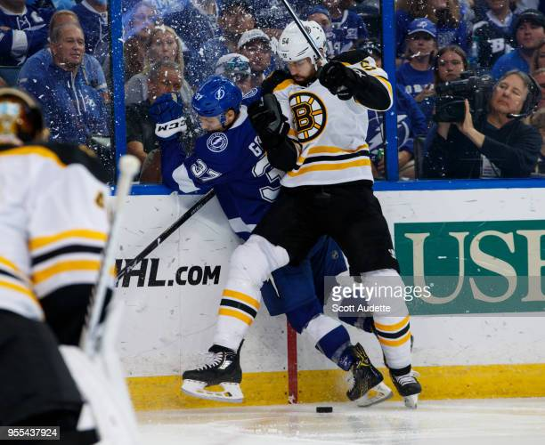 Yanni Gourde of the Tampa Bay Lightning is checked by Adam McQuaid of the Boston Bruins during Game Five of the Eastern Conference Second Round...