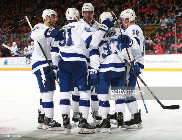 Yanni Gourde of the Tampa Bay Lightning is congratulated by his teammates after scoring a second period goal against the New Jersey Devils at the...
