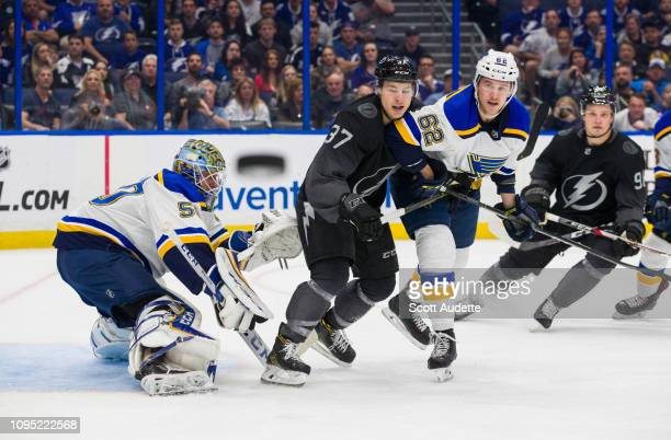 Yanni Gourde of the Tampa Bay Lightning looks for the puck against goalie Jordan Binnington and Mackenzie MacEachern of the St Louis Blues during the...