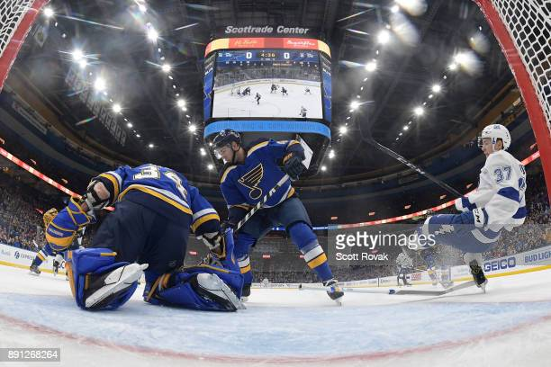 Yanni Gourde of the Tampa Bay Lightning trips over the stick of Jake Allen of the St Louis Blues as Jordan Schmaltz of the St Louis Blues defends the...
