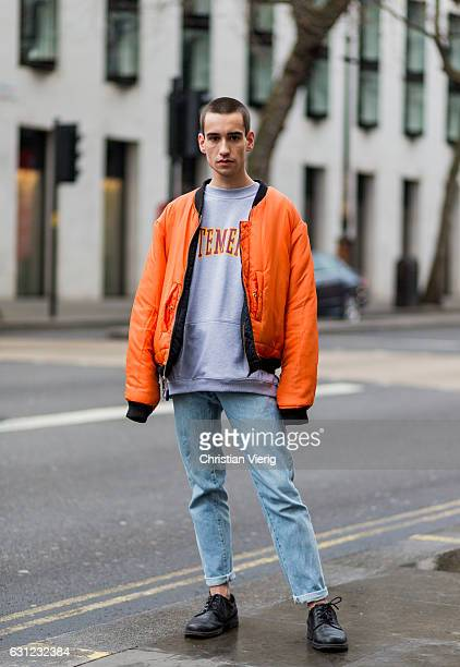 Yannic Hohaus wearing an orange bomber jacket grey sweater denim jeans leather shoes during London Fashion Week Men's January 2017 collections at...