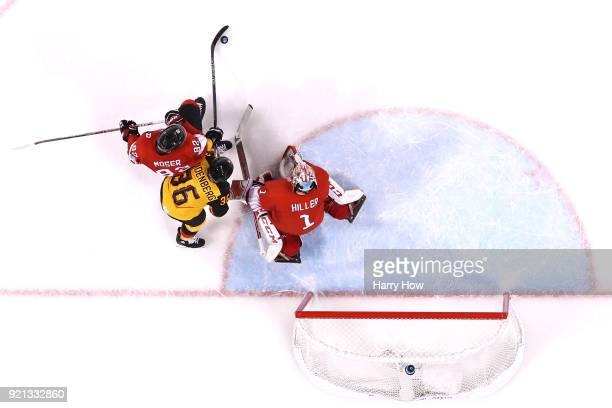 Yannic Seidenberg of Germany shoots and scores against Simon Moser and goalie Jonas Hiller of Switzerland in overtime during the Men's Ice Hockey...