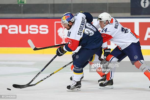Yannic Seidenberg of Munich and Joakim Hillding of Vaxjo during the Champions Hockey League Round of 32 match between Red Bull Munich and Vaxjo...