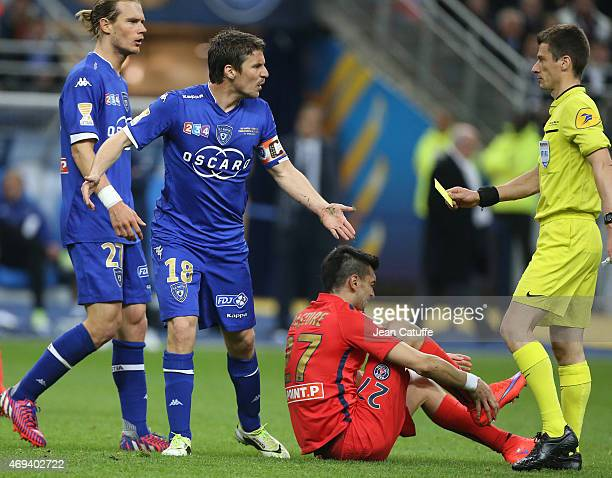 Yannick Cahuzac of Bastia receives a yellow card from referee Benoit Bastien during the French League Cup final between Paris SaintGermain FC and...