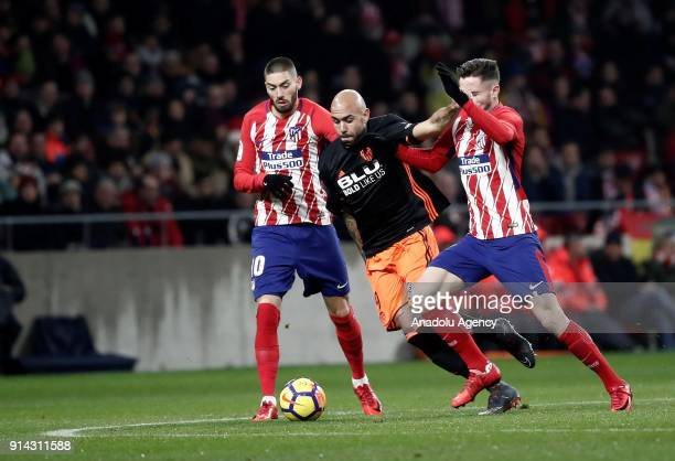 Yannick Carrasco and Saul Niguez of Atletico Madrid vie for the ball against Simone Zaza of Valencia during the La Liga match between Atletico Madrid...