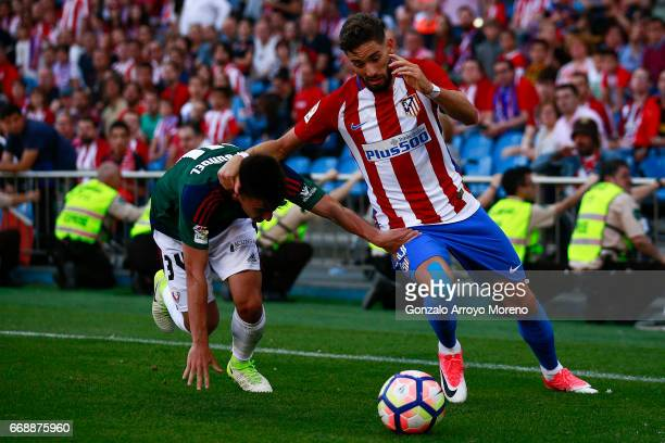 Yannick Carrasco of Atletico de Madrid competes for the ball with Aitor Bunuel of CA Osasuna during the La Liga match between Club Atletico de Madrid...
