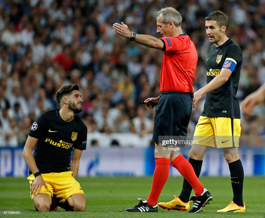 Yannick Carrasco of Atletico de Madrid, Gabi Fernandez of Atletico de Madrid and referree Martin Atkinson looks on during the UEFA Champions League semi-final first leg match between Real Madrid CF and Club Atletico de Madrid at Estadio Santiago Bernabeu on May 2, 2017 in Madrid, Spain.