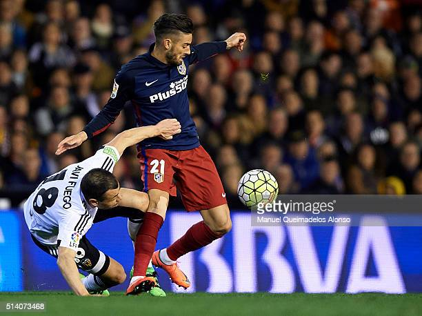 Yannick Carrasco of Atletico de Madrid is tackled by Javi Fuego of Valencia during the La Liga match between Valencia CF and Atletico de Madrid at...