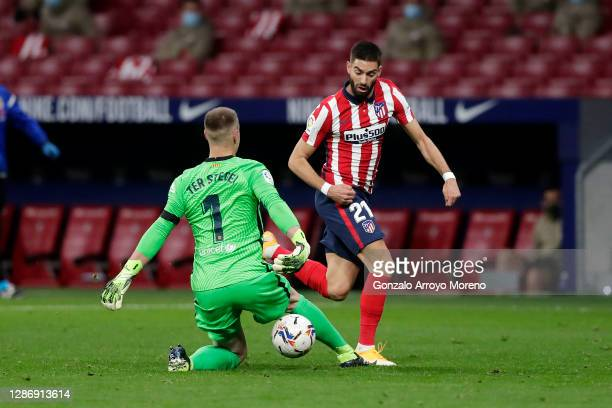 Yannick Carrasco of Atletico de Madrid runs with the ball past Marc-Andre ter Stegen of FC Barcelona on his way to scoring his team's first goal...