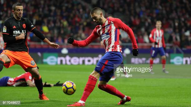 Yannick Carrasco of Atletico Madrid and a player of Valencia battle for the ball during the La Liga match between Atletico Madrid and Valencia at...