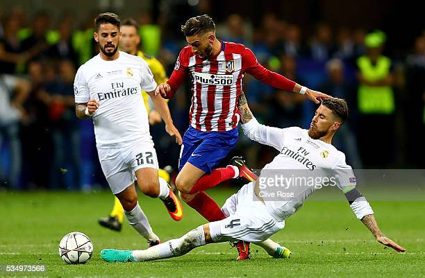 Yannick Carrasco of Atletico Madrid is challenged by Sergio Ramos of Real Madrid during the UEFA Champions League Final match between Real Madrid and...