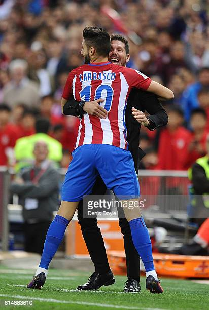 Yannick Carrasco of Club Atletico de Madrid celebrates with his Manager Diego Simeone after scoring his 3rd goal during the La Liga match between...