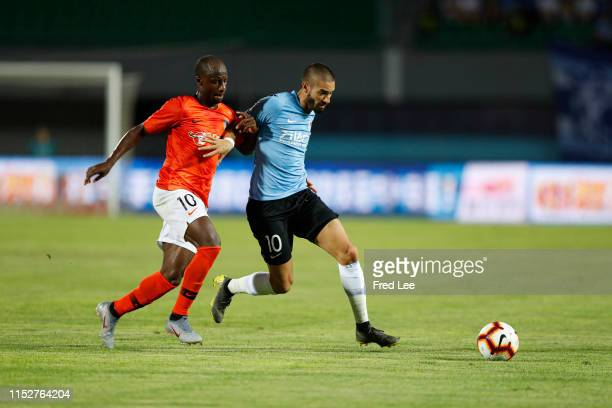 Yannick Carrasco of Dalian Yifang and Sone Aluko of Beijing Renhe in action during 2019 China Super League between Beijing Renhe and Dalian Yifang at...