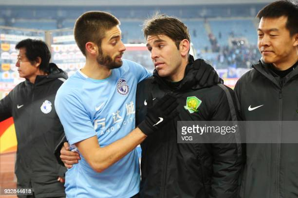 Yannick Carrasco of Dalian Yifang chats with Jonathan Soriano of Beijing Guoan after the 2018 Chinese Football Association Super League third round...