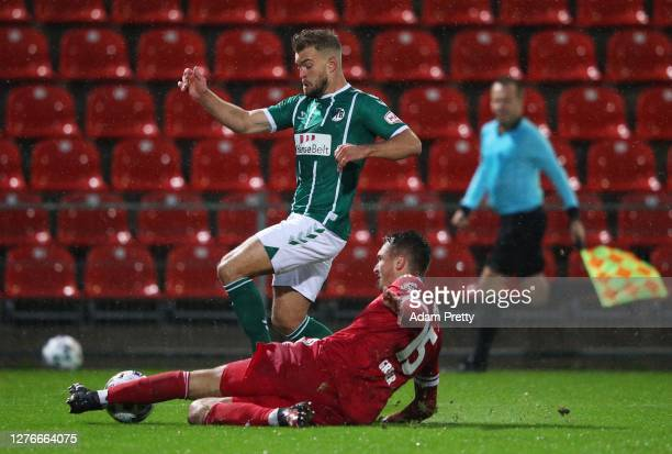 Yannick Deichmann of VfB Luebeck is tackled by Christoph Greger of SpVgg Unterhaching during the 3. Liga match between SpVgg Unterhaching and VfB...