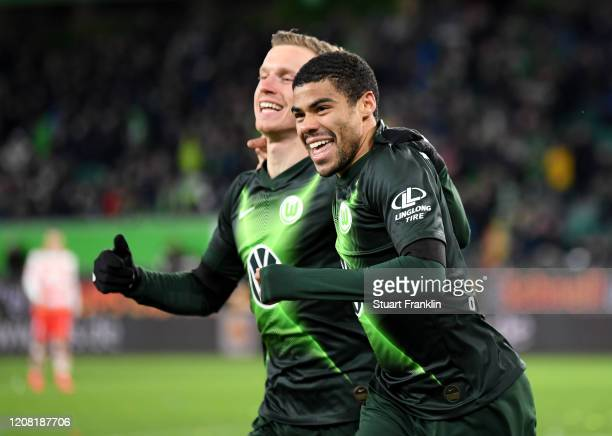 Yannick Gerhardt of VfL Wolfsburg celebrates with teammate Paulo Otavio after scoring his team's third goal during the Bundesliga match between VfL...