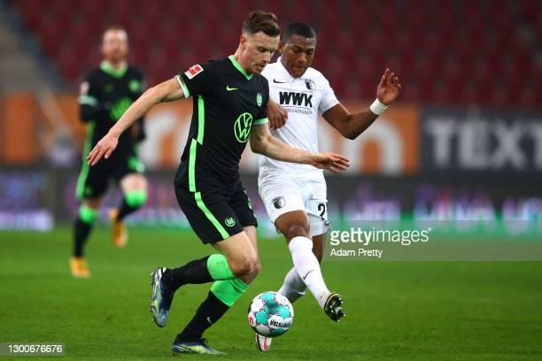 Yannick Gerhardt of VfL Wolfsburg is challenged by Fredrik Jensen of FC Augsburg during the Bundesliga match between FC Augsburg and VfL Wolfsburg at...