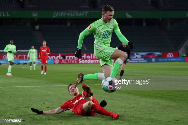 Yannick Gerhardt of VfL Wolfsburg jumps with the ball clear of Marcel Halstenberg of RB Leipzig during the Bundesliga match between VfL Wolfsburg and...