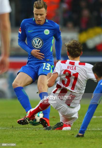 Yannick Gerhardt of Wolfsburg and Birk Risa of Koeln battle for the ball during the Bundesliga match between 1 FC Koeln and VfL Wolfsburg at...