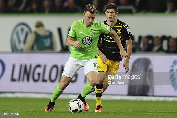 Yannick Gerhardt of Wolfsburg and Christian Pulisic of Dortmund compete for the ball during the during the Bundesliga match between VfL Wolfsburg and...
