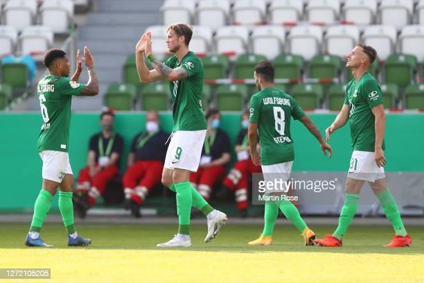 Yannick Gerhardt of Wolfsburg celebrates his team's third goal with teammates during the DFB Cup first round match between FSV Union Fürstenwalde and...
