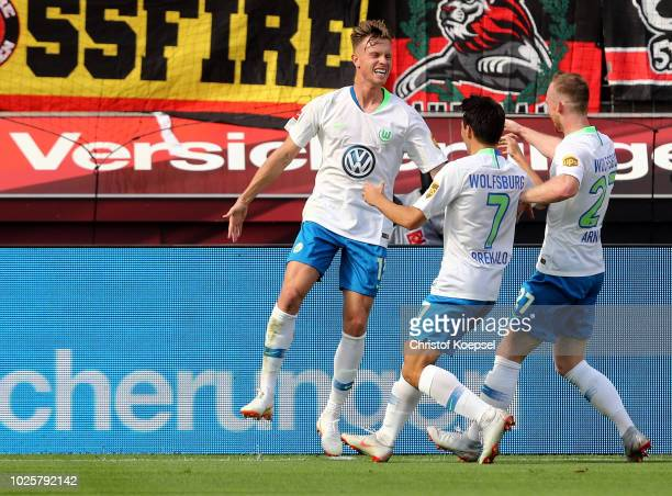 Yannick Gerhardt of Wolfsburg celebrates the first goal with Josip Breaklo and Maximilian Arnold of Wolfsburg during the Bundesliga match between...