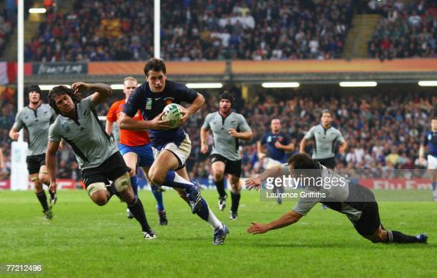 Yannick Jauzion of France avoids the tackle of Leon MacDonald of New Zealand on his way to scoring a try during the Quarter Final of the Rugby World...