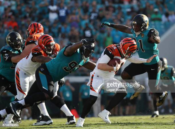 Yannick Ngakoue and Calais Campbell of the Jacksonville Jaguars put pressure on Andy Dalton of the Cincinnati Bengals in the second half of their...