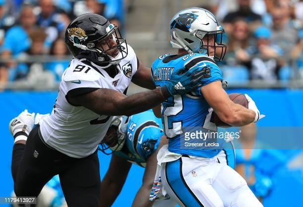Yannick Ngakoue of the Jacksonville Jaguars tries to sotp Christian McCaffrey of the Carolina Panthers during their game at Bank of America Stadium...