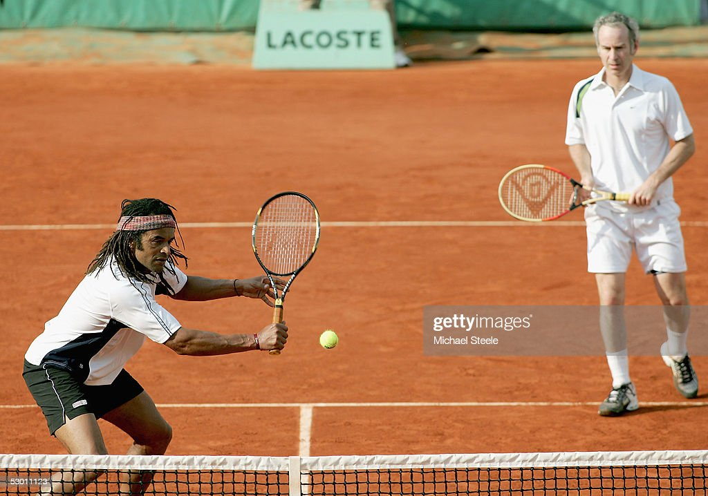 Yannick Noah of France and John McEnroe of USA in action during the over 35's doubles match during the eleventh day of the French Open at Roland Garros on June 2, 2005 in Paris, France.