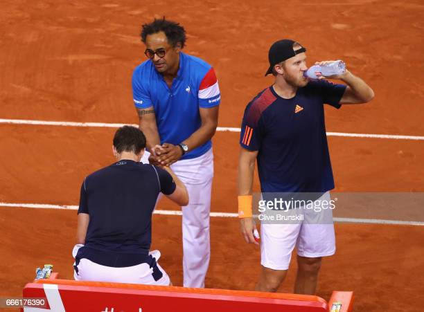 Yannick Noah the France captain consoles Jamie Murray and Dominic Inglot of Great Britain after the doubles match against Julien Benneteau and...