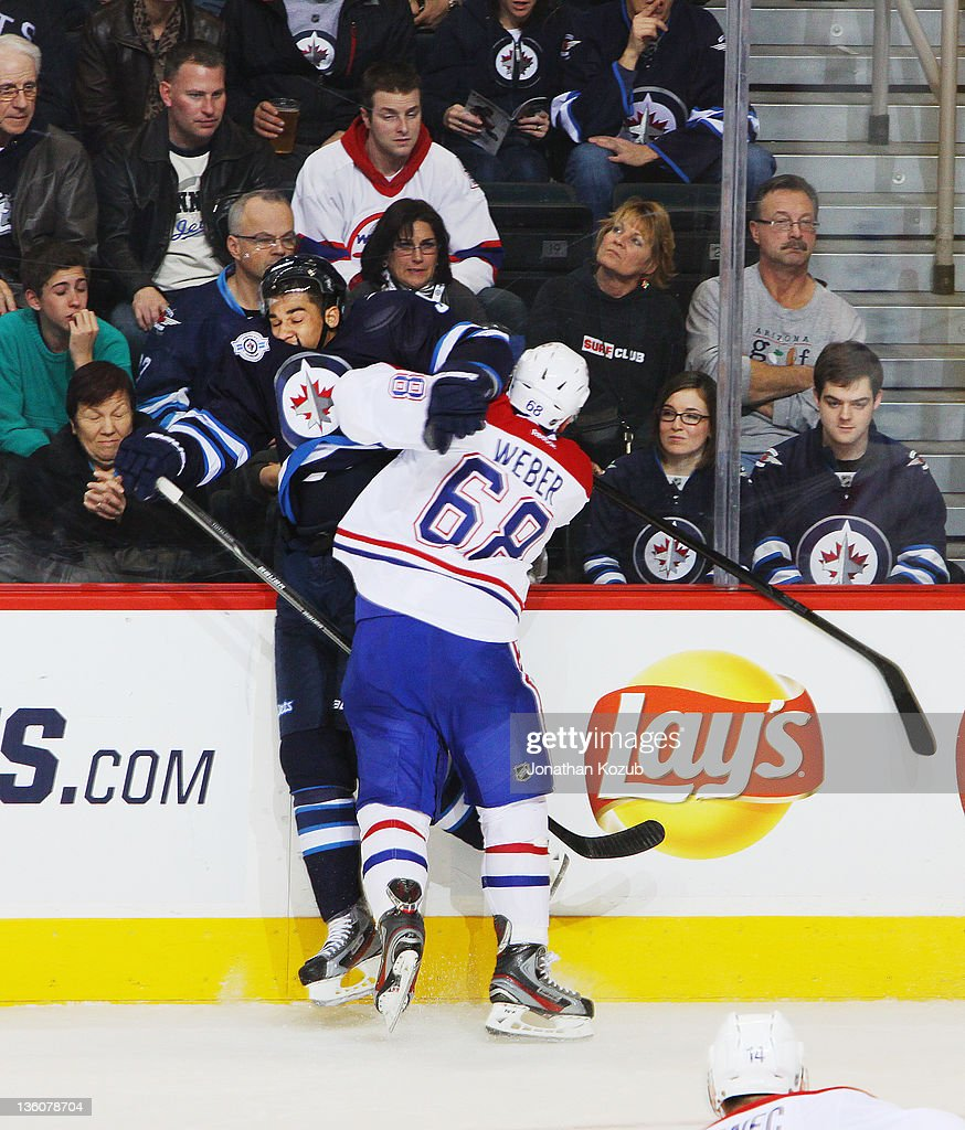 Yannick Weber #68 of the Montreal Canadiens checks Evander Kane #9 of the Winnipeg Jets into the boards during third period action at the MTS Centre on December 22, 2011 in Winnipeg, Manitoba, Canada.
