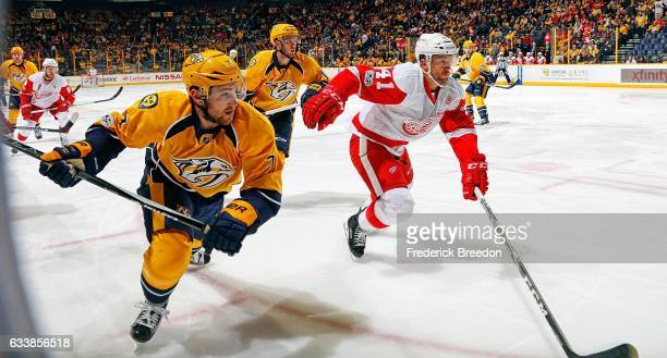 Yannick Weber of the Nashville Predators skates against Luke Glendening of the Detroit Red Wings during the second period at Bridgestone Arena on...