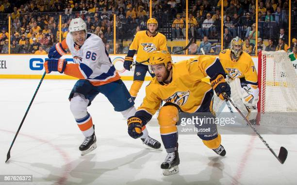 Yannick Weber of the Nashville Predators skates against Nikolay Kulemin of the New York Islanders during an NHL game at Bridgestone Arena on October...
