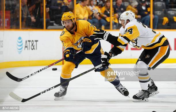 Yannick Weber of the Nashville Predators skates against the Tom Kuhnhackl of the Pittsburgh Penguins during an NHL game at Bridgestone Arena on...